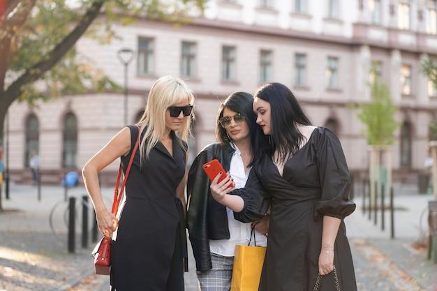 Glückliche gruppe von drei freunden mit einem smartphone, das auf der straße steht. freundschafts-, technologie- und freizeitkonzept. freudige model freundinnen lächelnd haben eine gute zeit.