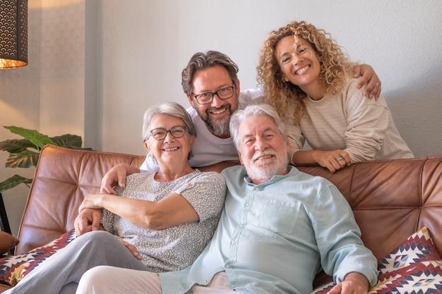Glückliche gruppe von familie, die zu hause auf dem sofa sitzt und sich entspannt, zeit zusammen verbringen. schöne leute, eltern und erwachsene söhne, zwei generationen, die in die kamera schauen
