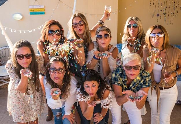 Glückliche gruppe von frauen, die mit konfetti und lächeln einen geburtstag feiern. freundschaftskonzept. entspannung und glück für neun weibliche menschen