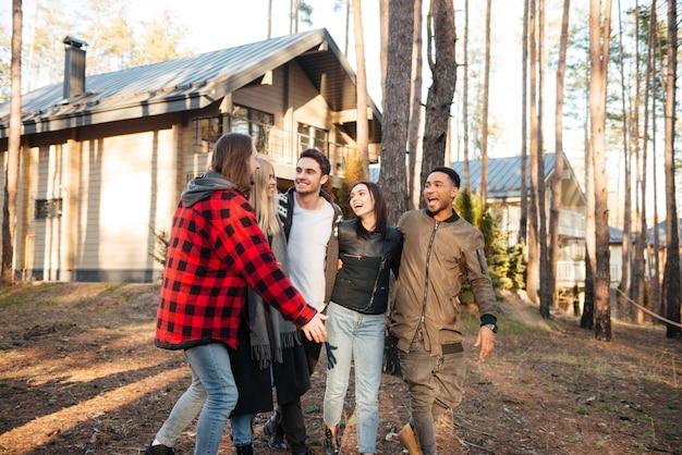 Glückliche gruppe von freunden, die draußen im wald gehen.