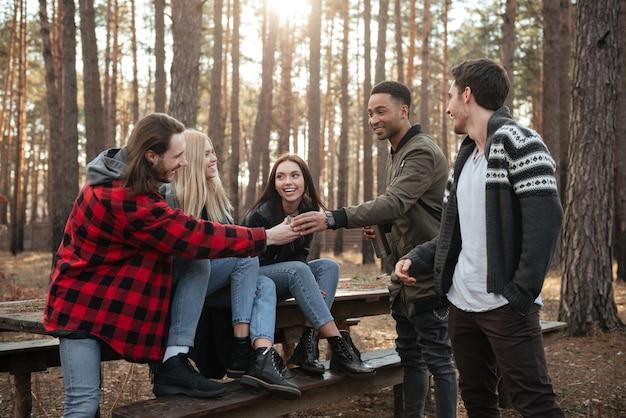 Glückliche gruppe von freunden, die draußen im wald sitzen.