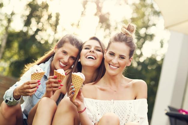 Glückliche gruppe von freunden, die im freien eis essen