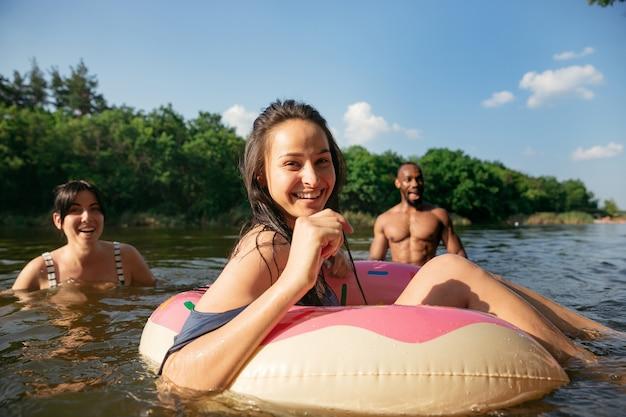 Glückliche gruppe von freunden, die spaß beim lachen und schwimmen im fluss haben. freudige männer und frauen mit gummiringen als donut am flussufer an einem sonnigen tag. sommerzeit, freundschaft, resort, wochenendkonzept.