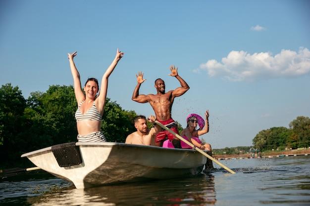 Glückliche gruppe von freunden, die spaß beim lachen und schwimmen im fluss haben