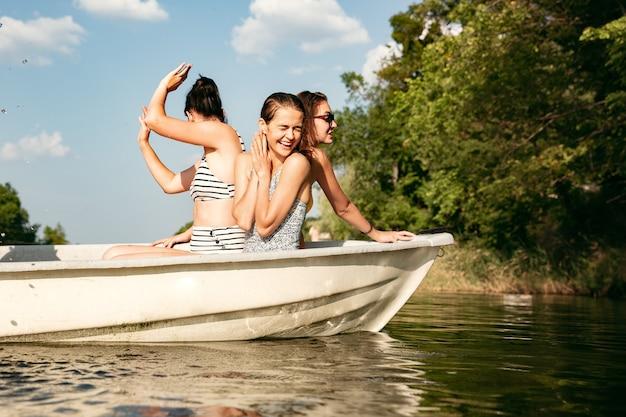 Glückliche gruppe von freunden, die spaß haben, während sie lachen, wasser spritzen und im fluss schwimmen. freudige frauen im badeanzug in einem boot am flussufer am sonnigen tag. sommerzeit, freundschaft, resort, wochenendkonzept.