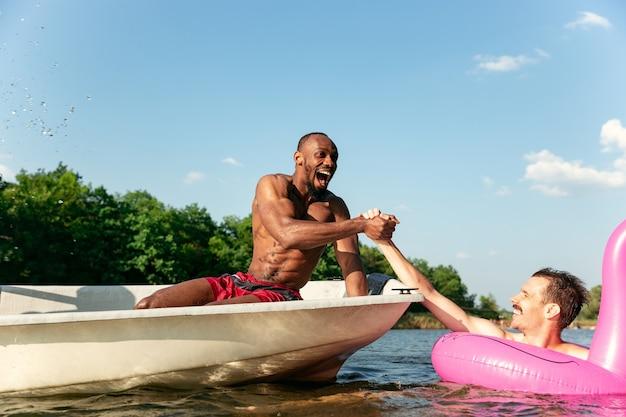 Glückliche gruppe von freunden, die spaß haben, während sie lachen, wasser spritzen und im fluss schwimmen. freudige männer im badeanzug in einem boot am flussufer an sonnigem tag. sommerzeit, freundschaft, resort, wochenendkonzept.