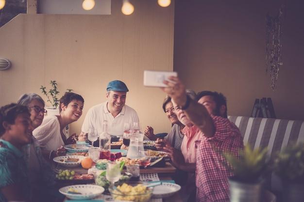 Glückliche gruppe von menschen in familienfreundschaft, die alle zusammen feiern und ein schönes abendessen im freien zu hause auf der terrasse genießen