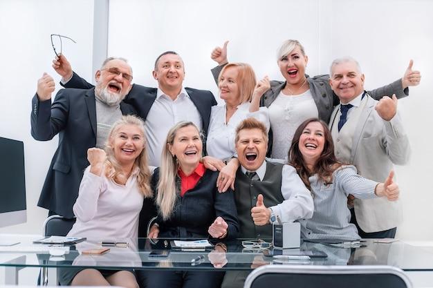Glückliche gruppe von professionellen fachleuten, die daumen nach oben zeigen.