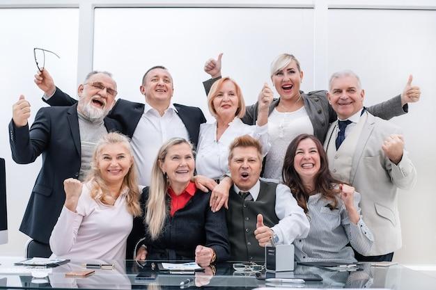 Glückliche gruppe von professionellen profis, die daumen hoch zeigen. das konzept der professionalität
