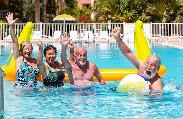Glückliche gruppe von senioren, die volleyball im schwimmbad mit aufblasbarem netz und ball spielen. gewinner mit glück und lächeln. strahlende sonne im sommer