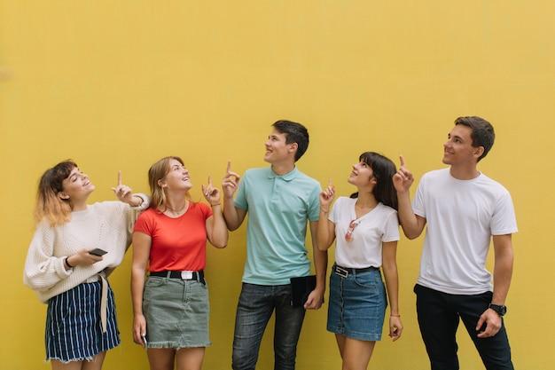 Glückliche gruppenjugendliche zeigen etwas auf dem gelben hintergrund des kopienraumes.