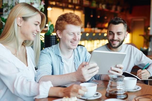 Glückliche gruppenmitglieder, die das touchpad-display betrachten, das von einem der jungs gehalten wird, während sie sich auf das seminar oder projekt im college-café vorbereiten