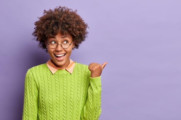 Glückliche gut aussehende ethnische frau mit afro-haaren zeigt auf leerzeichen