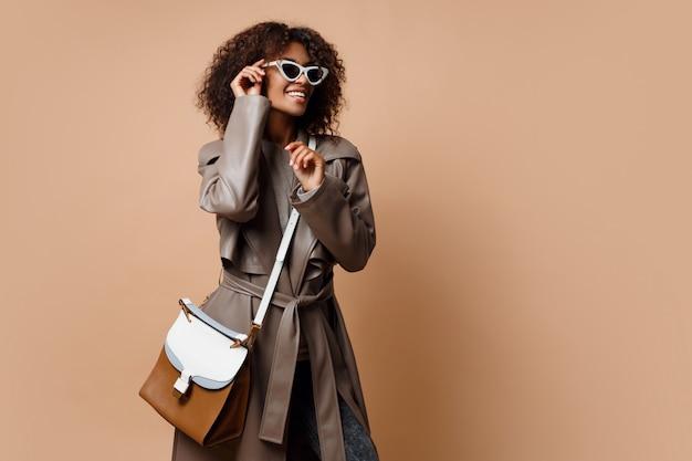 Glückliche gut aussehende schwarze frau, die grauen ledermantel trägt und auf beigem hintergrund aufwirft. herbst- oder wintermodekonzept.