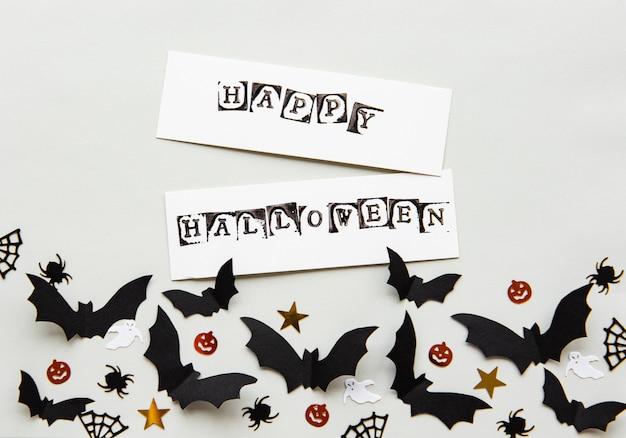Glückliche halloween-grußkarte mit dekorativen schlägern
