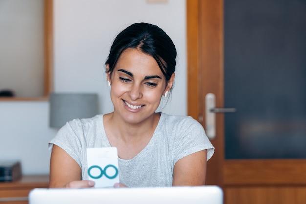 Glückliche handwerkerin lächelt und zeigt ihre hausgemachten ohrringe in einem arbeitsvideoanruf.