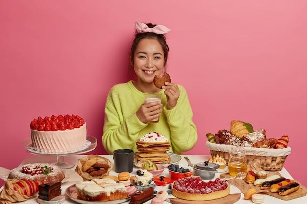 Glückliche hausfrau backte viele leckere desserts, wartet auf ehemann, hat leckeres frühstück, isst haferkekse mit milch, posiert drinnen.