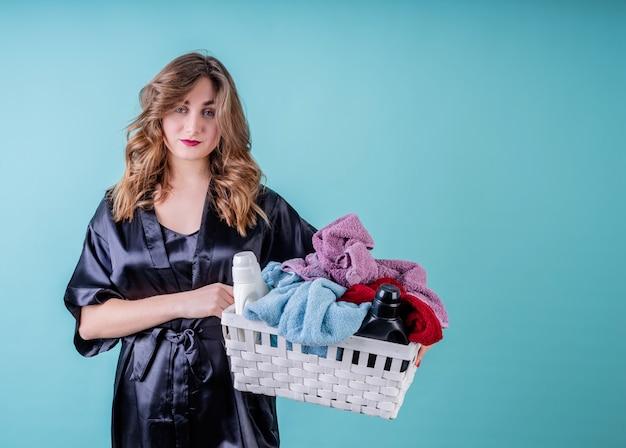 Glückliche hausfrau, die einen korb der kleidung bereit hält für wäsche lokalisiert auf blauer wand