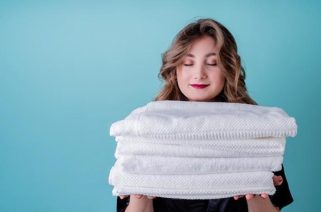 Glückliche hausfrau, die einen stapel sauberer weißer handtücher auf blauer wand isoliert hält