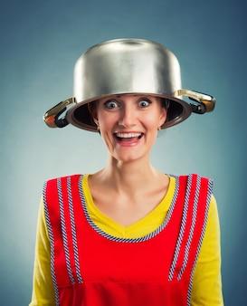 Glückliche hausfrau mit sause pan auf dem kopf