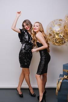 Glückliche helle partyfeier von zwei erstaunlichen attraktiven jungen frauen in den luxuriösen schwarzen kleidern, die spaß auf weißer wand haben. große luftballons voller goldener lametta, geschenke, die positivität ausdrücken.