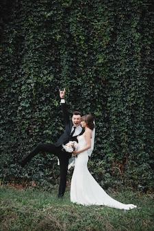 Glückliche herrliche braut und stilvoller bräutigam, die spaß, hochzeitspaar, luxushochzeit springt und hat. lustige und verrückte bräute
