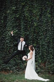 Glückliche herrliche braut und stilvoller bräutigam, die spaßspaß und verrückte bräute springt und hat