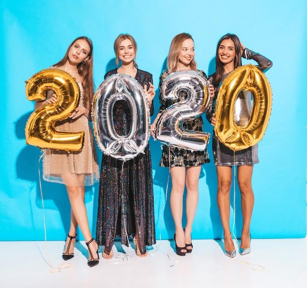 Glückliche herrliche mädchen in den stilvollen sexy party-kleidern, die gold und silber 2020 ballone halten