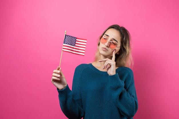 Glückliche herzförmige brille der jungen frau, die amerikanische flagge gegen einen rosafarbenen hintergrund des studios hält