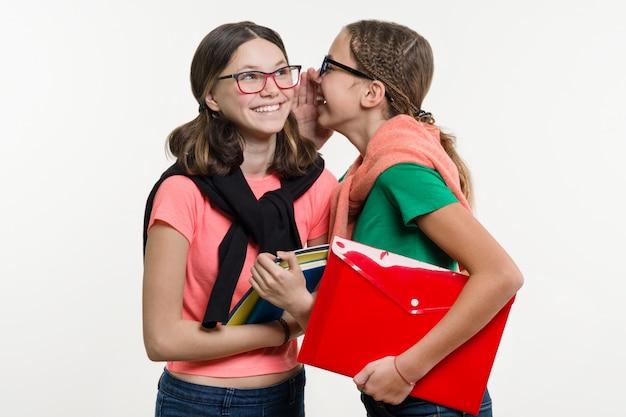 Glückliche high-school-freunde sind teenager-mädchen, reden und geheim.