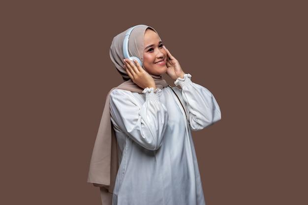 Glückliche hijab-frauen, die drahtlose kopfhörer verwenden, genießen es, musik zu hören