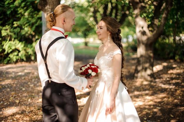 Glückliche hipster-braut und bräutigam, die im wald zwischen grünen bäumen am warmen sommertag gehen