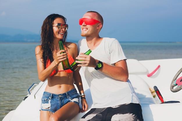 Glückliche hipster-frau und mann, die bier im tropischen sommerurlaub in thailand trinken, das auf boot im meer reist, party am strand, leute, die spaß zusammen haben, positive emotionen