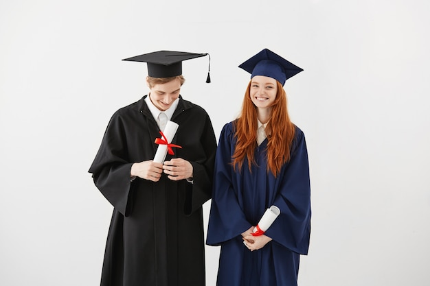 Glückliche hochschulabsolventen in den lächelnden mänteln, die diplome halten.