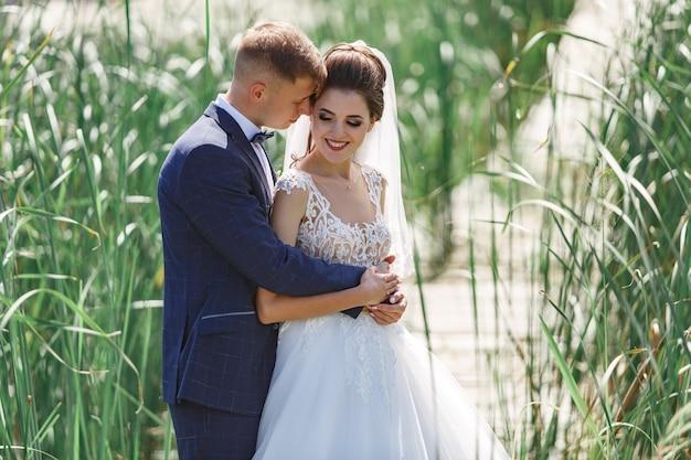Glückliche hochzeitspaare, die auf holzbrücke gehen. emotionale braut und bräutigam, die leicht draußen umarmen.