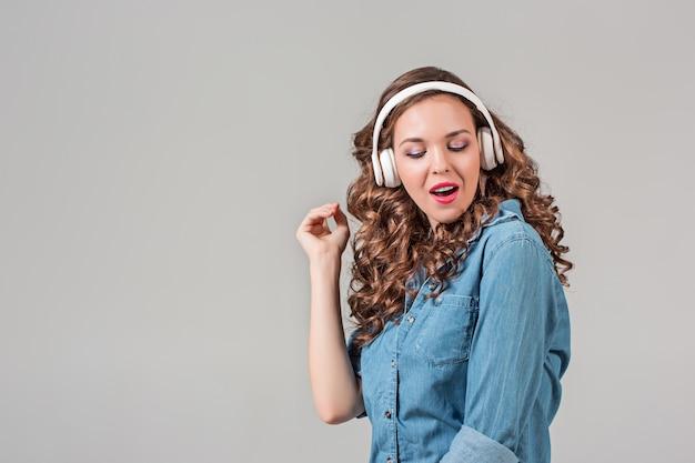 Glückliche hörende musik der jungen frau mit kopfhörern. isoliertes porträt auf grauer wand