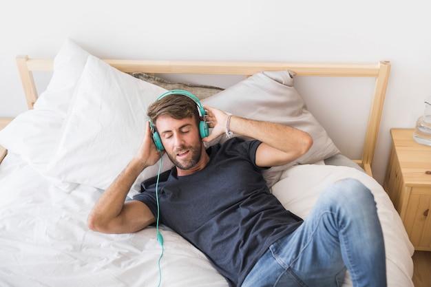 Glückliche hörende musik des jungen mannes auf dem bett