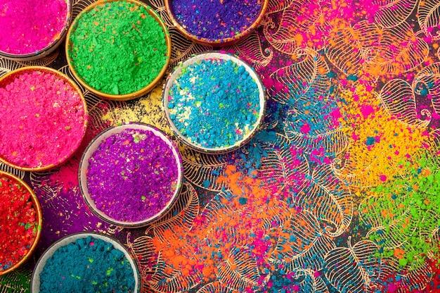 Glückliche holi-draufsicht auf bunte holi-farben in schalen mit splash, konzept-indisches farbfestival.