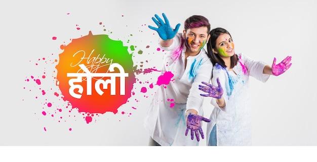 Glückliche holi-grußkarte, die junge indische paare zeigt, die farben auf weißem hintergrund spielen