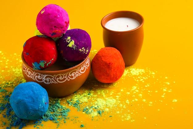 Glückliche holi-grußkarte entworfen, die indisches traditionelles süßes getränk zeigt, pulverfarbenball angeordnet auf gelber oberfläche