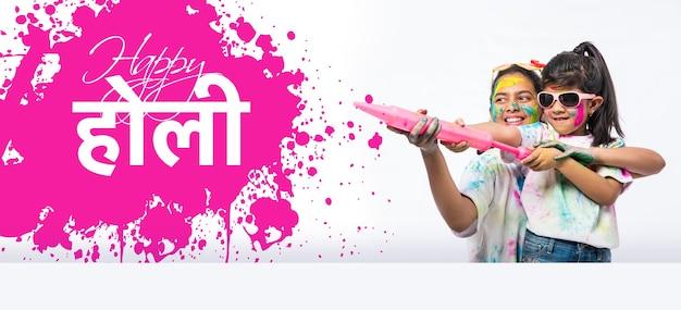 Glückliche holi-grußkarte - indische kleine kinder oder freunde oder geschwister, die das holi-fest mit gulal- oder puderfarbe, süßigkeiten, pichkari oder spray feiern