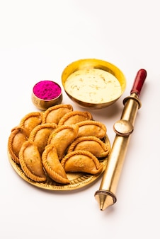 Glückliche holi-grußkarte. süße jalebi, jilapi, zulbia, mushabak oder zalabia mit thandai-getränk und gulal-farbe auf weiß arrangiert