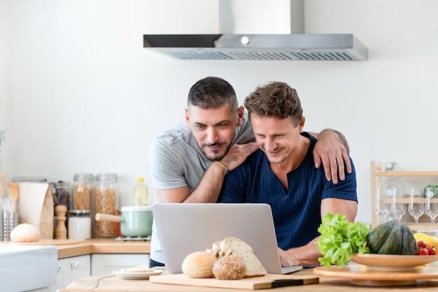 Glückliche homosexuelle männliche paare unter verwendung des internets zusammen zu hause