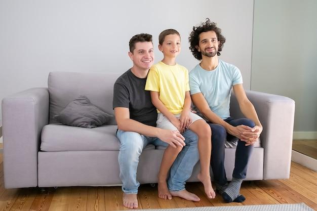 Glückliche homosexuelle väter und kind sitzen zu hause auf der couch, lächeln und schauen weg. speicherplatz kopieren. familien- und elternschaftskonzept