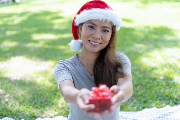 Glückliche hübsche asiatische dame, die sankt-hut trägt und geschenkbox gibt