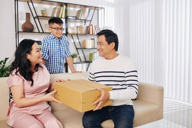 Glückliche hübsche asiatische frau, die geburtstagsgeschenk von ehemann und sohn empfängt