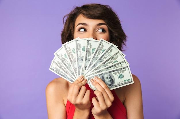 Glückliche hübsche brünette frau, die ihr gesicht mit geld bedeckt