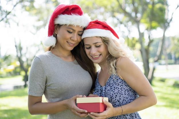 Glückliche hübsche damen, die sankt-hüte tragen und geschenkbox halten