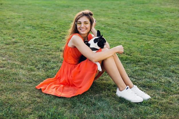 Glückliche hübsche frau, die auf gras im park sitzt, boston-terrier-hund hält, positive stimmung lächelt, orange kleid trägt, trendigen stil, schlanke beine, turnschuhe, spielt mit haustier, sommermodetrend