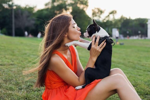 Glückliche hübsche frau, die auf gras im sommerpark sitzt, boston-terrier-hund hält, küsst, orange kleid trägt, trendigen stil, spielt mit haustier